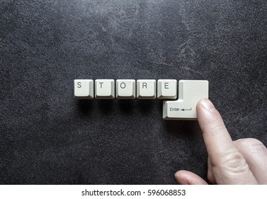 Internet shopping concept: Word store written using keyboard keys and index finger of a man's hand presses on the enter