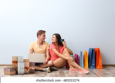 Internet shopping concept. Young couple sitting with laptop and purchases near wall at home