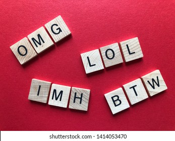 Internet slang. Acronyms : BTW (By The Way), OMG, LOL and IMH used as abbreviations in text messages, in wooden alphabet letters on a bright yellow background