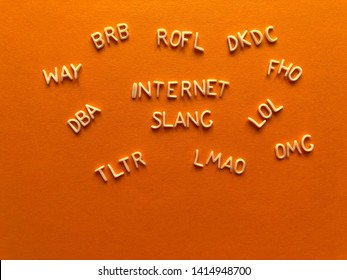 Internet slang, acronyms including ROFL, (Rolling on floor laughing) LOL (Lots of Laughs), LMAO, TLTR, DBA, WAY, BRB, in alphabet letters on a bright orange background with copy space