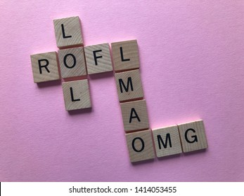 Internet slang. Acronyms : LOL (laughing out loud), ROFL, OMG, and LMAO used as abbreviations in text messages, in wooden letters in crossword form, on a pink background with copy space.
