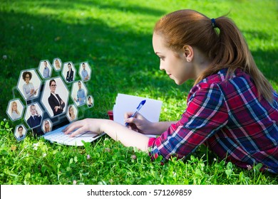internet and social network concept - teenage girl lying on green in park and using laptop