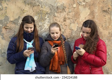 Internet and social networks replace live communication. Three girls together chat using their smartphones outdoor - horizontal