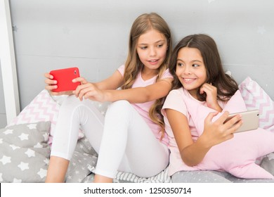 Internet surfing and absence parental advisory. Smartphone internet access. Girls sisters wear pajama busy with smartphones. Children in pajama interact with smartphones. Application for kids fun.