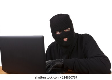 Internet Theft - a man wearing a balaclava sat behind a laptop, white background.