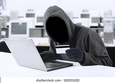 Internet Theft - a man wearing a balaclava and holding a credit card while sat behind a laptop,