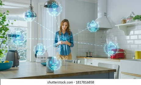 Internet of Things Concept: Young Woman Using Smartphone in Kitchen. She controls her Kitchen Appliances with IOT. Graphics Showing Digitalization Visualization of Connected Home Electronics Devices