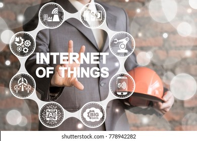Internet Of Things. IOT Industry 4.0. Man with hard hat using virtual interface offers internet of things text icon.