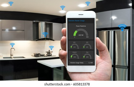 Internet of things , iot , smart home , kitchen , network connect concept. Human hand holding white phone, smart home application to count power usage application and wifi icon with kitchen background