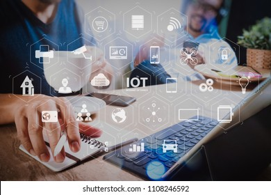 Internet of Things (IOT) technology with AR (Augmented Reality) on VR dashboard. co working website designers working at office and holding a cup of coffee,working on smart phone and digital tablet.
