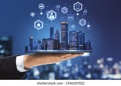 Internet of things in smart city concept with businessman hand holds digital tablet with night skyscrapers and digital social network icons