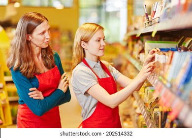 Internship organizing shelves in supermarket under supervision of the store manager