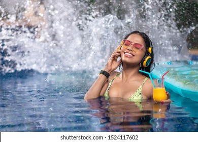 An interracial brunette is enjoying in a pool of clouds on a mattress with a cocktail in her hand, in yellow headphones and a wristwatch, yellow-pink sunglasses raised by her hand, a green bikini.