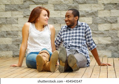 Interracial charming couple wearing casual clothes sitting on wooden surface posing for camera staring at each other, grey brick wall background