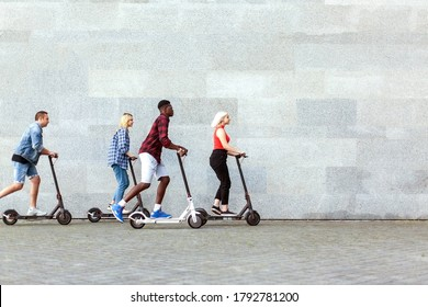 interracial company of friends rides electric scooters against the background of a wall, young people use eco transport in the city