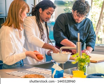 Interracial couple of African husband and Caucasian wife prepare food together with a professional chef