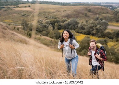 Interracial couple with backpacks walking on hill with grass during trip