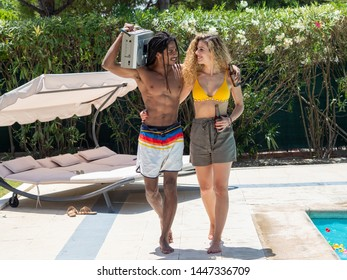Interracial couple, black man and Caucasian woman walk with a cassette radio by the pool