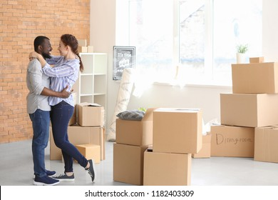 Interracial couple with boxes indoors. Moving into new house