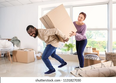 Interracial couple carrying big box in room. Moving into new house