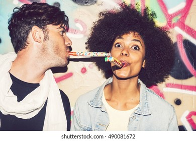 Interracial couple celebrating and playing with party blowers