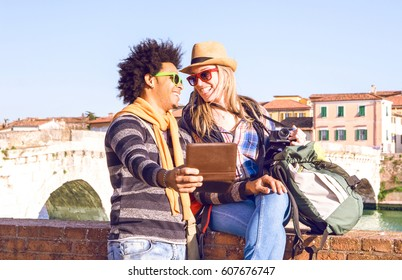 Interracial couple of friends travelers taking selfie in old town riverside at sunset - Happy young tourists looking at each other having fun moment with self romantic photo on city background