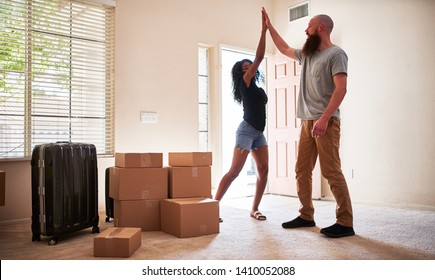 interracial couple giving each other a high five afrer moving into new house