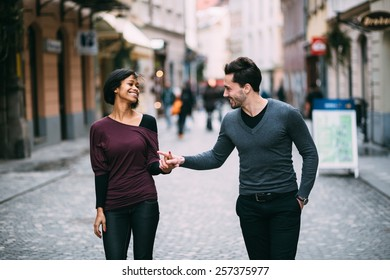 Interracial couple holding hands on the street