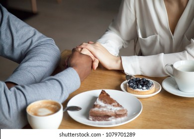 Interracial couple holding hands sit at cafe table, african black man and white woman in love enjoy date in coffee house concept, romantic biracial lovers meet in public place together, close up view