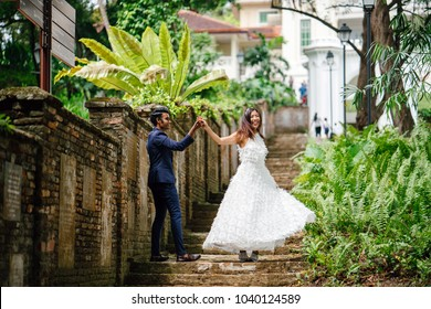 An interracial couple (Indian man, Chinese woman) pose for wedding photographs and portraits in a park in the day. They are on old stone steps and  and smiling and laughing as they take photos.