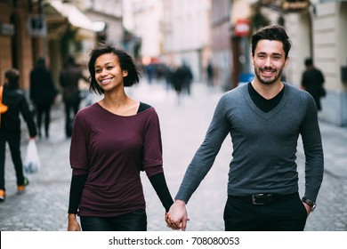 Interracial couple in love holding hands walking down the street