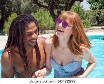 interracial couple in love, play in the pool. The girl very white and red hair and the boy black