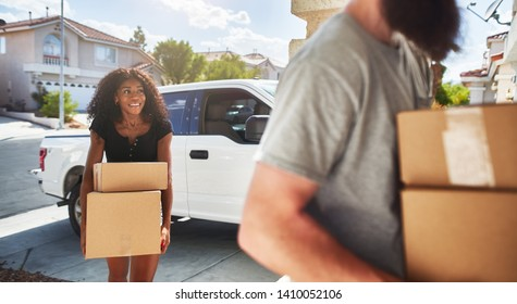 interracial couple moving into new home and taking boxes out of truck