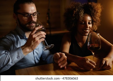 Interracial couple on date: handsome Caucasian man in shirt and glasses holding glass of red wine, sitting at table with his beautiful African girlfriend, enjoying nice evening together at restaurant