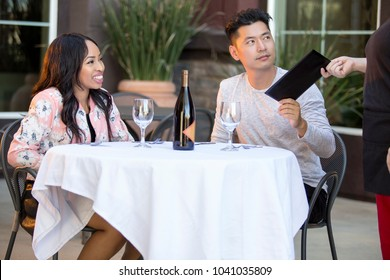 Interracial couple on a date paying for a restaurant tab with a waitress. They are in an outdoor cafe handling the payment bill and server tip or gratuity.