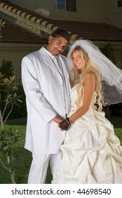 Interracial couple outdoors. Smiling laughing newlywed young Caucasian woman and mid aged ethnic black man of African American and Italian ethnicity