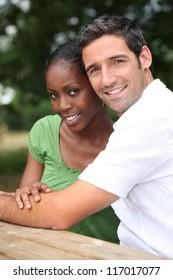 An interracial couple in a park.