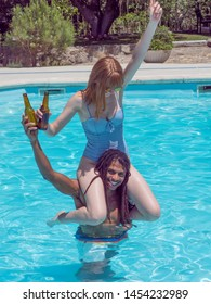 interracial couple play in the pool. She's on his shoulders and they drink beer.