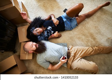 interracial couple relaxing after hard work moving by smoking marijuana joint together while laying on floor