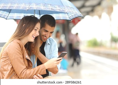 Interracial couple sharing a phone in a train station while wait under an umbrella in a rainy day