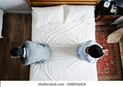 Interracial couple sitting back to back on the bed