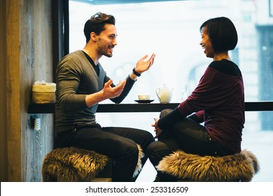 Interracial couple talking in coffee shop