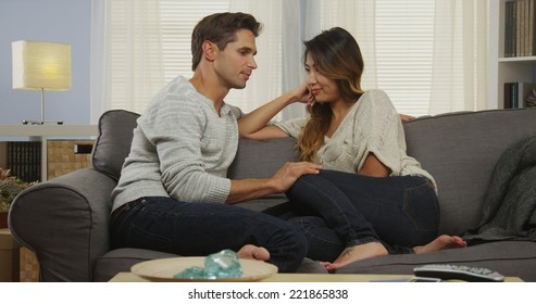 Interracial couple talking on couch