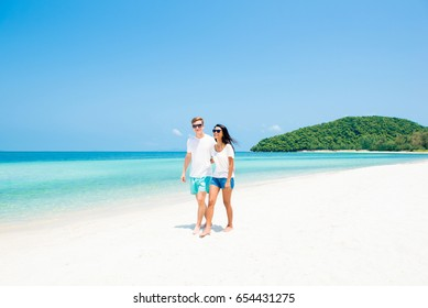 Interracial couple walking on beautiful beach in summer, Koh Samui Thailand - vacation and tourist concepts