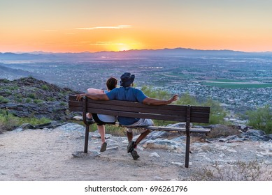 An interracial couple watches from Dobbins Lookout on South Mountain as the sun goes down over Phoenix, Arizona.