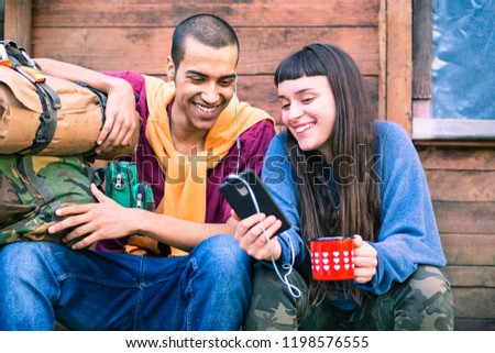 Interracial couple of young hikers looking at phone holding coffee - Happy teens on trekking outfit using smartphone sitting outdoor - Pretty girl showing video at friend - Mobile technology concept