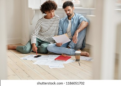 Interracial coworkes read written request for production more goods, study resale price sit together on floor at home, busy with deciding financial problems, drink coffee and use modern technoligies.