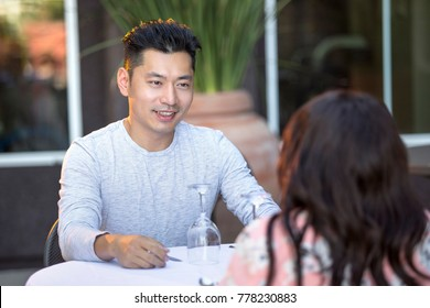 Interracial dating asian male and black female couple in an outdoor restaurant or cafe.  They are flirting and talking on a table.  The image depicts relationships and romance.