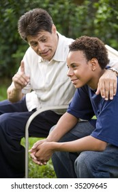 Interracial father and teenage son together in back yard