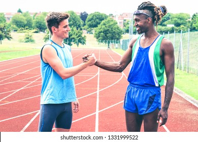 Interracial friends greeting each other handshaking at the stadium running track - Runners shake hands in sign of mutual respect in life and in sport - Concept of friendship and  equality  Image